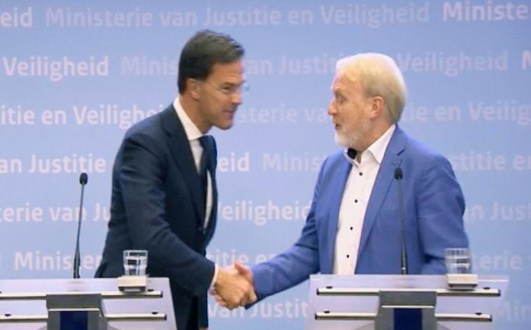 Kort nadat Mark Rutte alle Nederlanders opriep te stoppen met het schudden van handen, gaf hij Jaap van Dissel een hand. Beeld AP