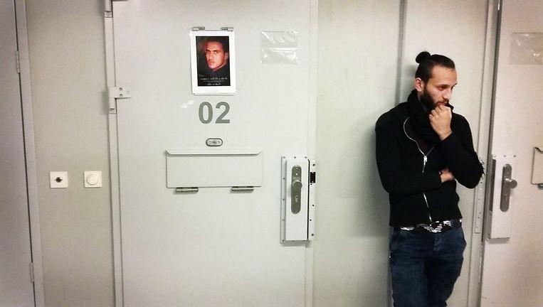 Krar Mehdi (22) voor de deur van de kamer (voorheen cel) van Hussein in de noodopvang. Krar vluchtte samen met Hussein naar Europa. Beeld Wilfred van de Poll