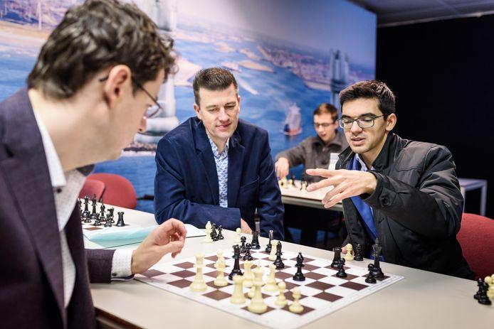 Anish Giri (rechts) analyseert zijn partij met coach Erwin l'Ami en Jeroen Bosch (midden). Ook de schaakwereld staat stil na het afgebroken kandidatentoernooi.