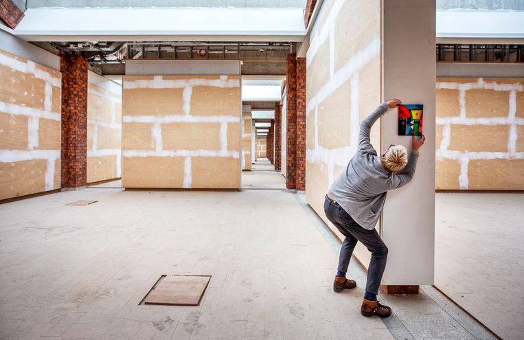 Makelaar Geert Klaver  in Opmeer bij het enige schilderij in het onafgebouwde Scheringa Museum voor Realisme. Beeld Raymond Rutting / de Volkskrant