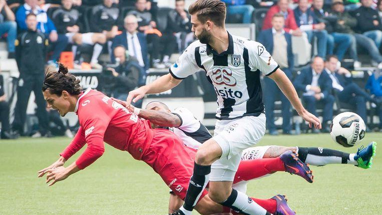 Heracles Almelo-speler Lerin Duarte haalt Enes Ünal neer, Robin Pröpper helpt hem. Beeld anp