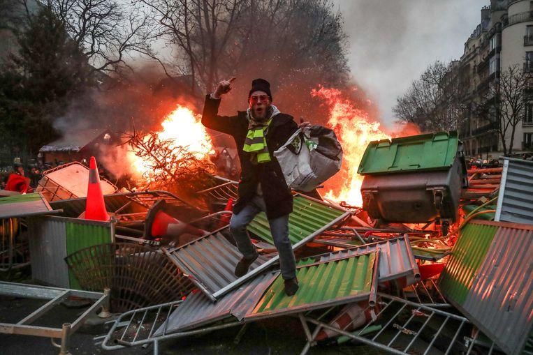 Een demonstrant op een barricade in Parijs, zaterdag. Beeld AFP