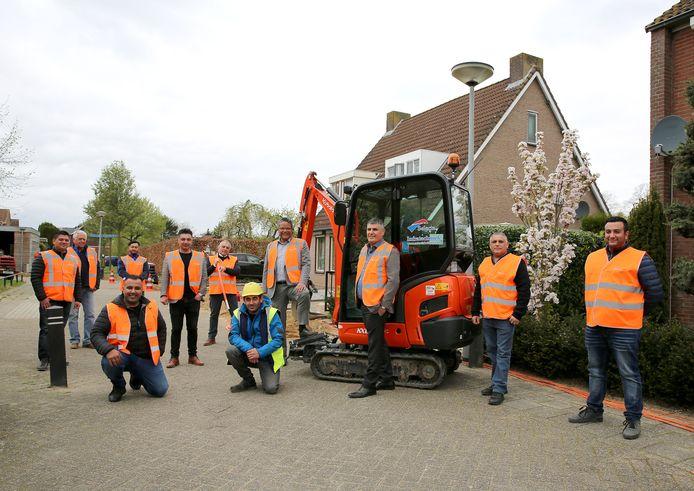 Wethouder Stefan van Someren (in grijs pak en oranje hesje) bij de start van de graafwerkzaamheden voor de glasvezel in IJzendoorn