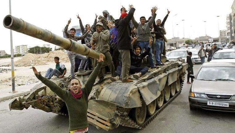 Blije opstandelingen in Benghazi, op een tank die ze buit zouden hebben gemaakt van troepen van Kadhafi. Beeld reuters