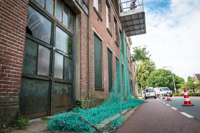Bij de paupervilla aan de Boven Havenstraat zijn netten gespannen om te voorkomen dat puin van het pand de straat op waait.