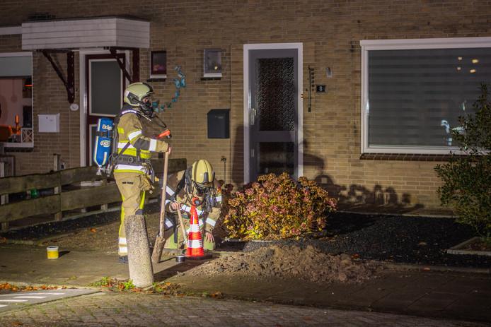 Brandweerlieden trachten het gaslek in de Hortensiastraat in Woerden te dichten.
