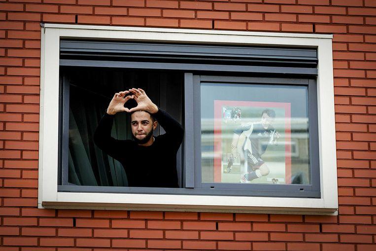 Mohammed, de broer van Abdelhak Nouri, groet de fans vanuit het raam van zijn huis. Beeld anp
