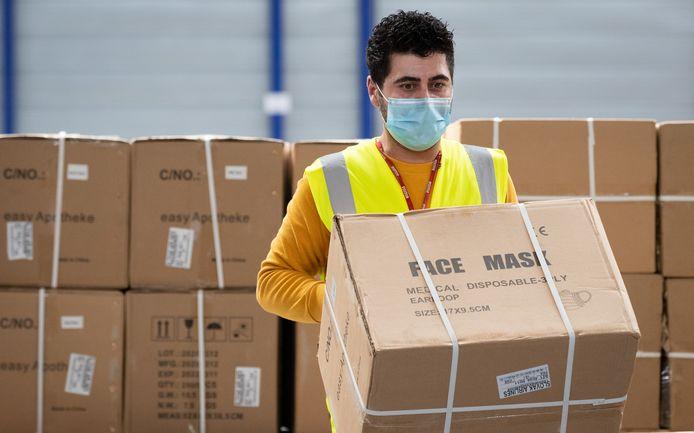 Un travailleur de Liege Airport manipulant une caisse de masques chirurgicaux en avril dernier.