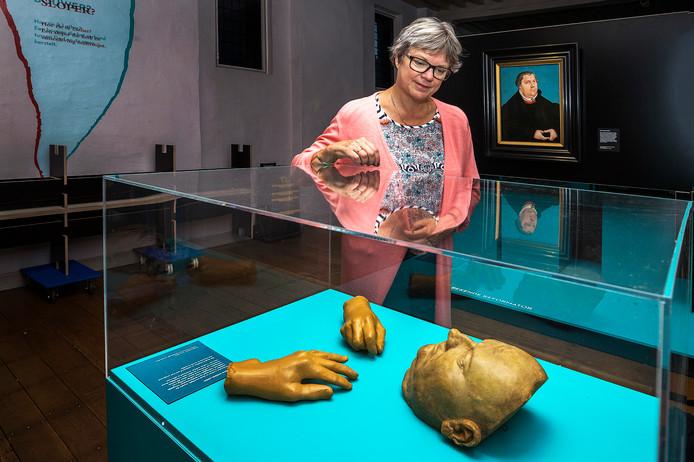 Conservator Tanja Kootte van Museum Catharijneconvent bij de vitrine met het dodenmasker van Maarten Luther. Op de achtergrond een portret van Luther van Lucas Cranach.