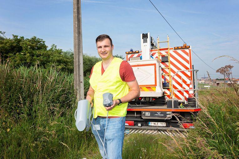 Een medewerker van Fluvius toont de sensor die in Veurne zal geplaatst worden