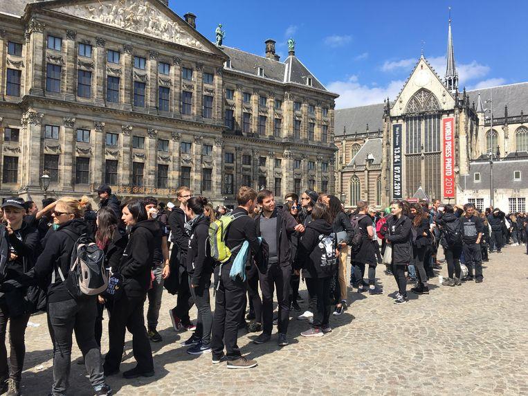 Van Madame Tussauds tot aan de Nieuwendijk stond een lange rij demonstranten te wachten om zich voor het 'levende' vierkant aan te melden.  Beeld Hannah Stöve