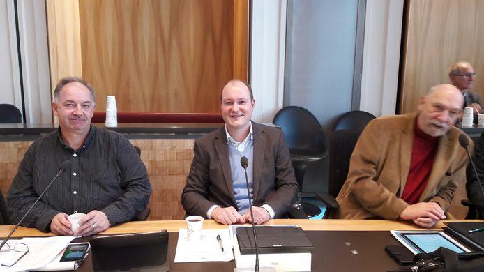 Het kersverse VVD-raadslid Peter Stoel neemt plaats tussen fractiegenoot Albert van der Giessen (links) en Pim Kraan (rechts) op een raadszetel.