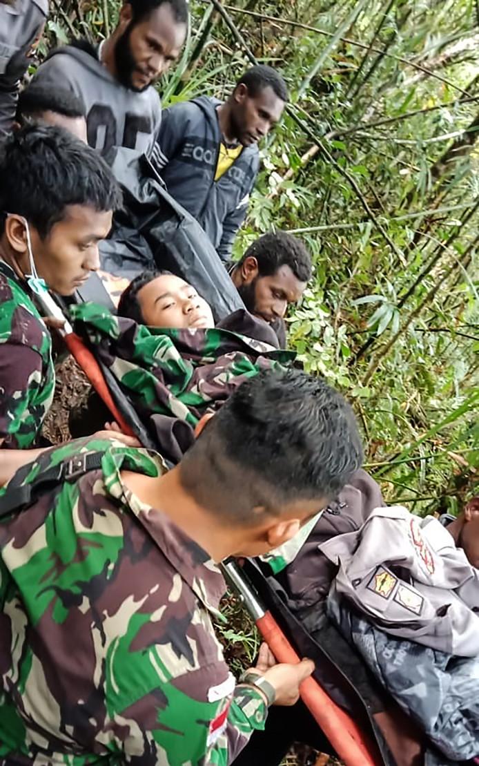 Militairen brengen de enige overlevende van de crash in veiligheid.