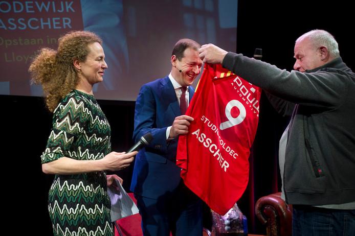 'Deventer Overlever' Carel Roelvink overhandigt het Go Ahead Eagles-shirt aan Lodewijk Asscher. Presentatrice van de avond, Hadassah de Boer, kijkt toe.
