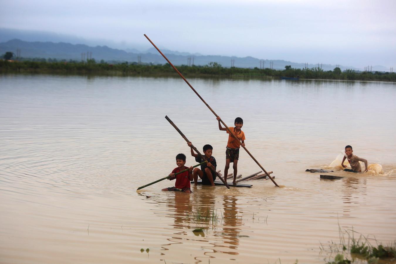 Kinderen op een geïmproviseerd vlot van bamboe in de staat Rakhine in Myanmar, nadat de regio werd getroffen door hevige moessonregens.
