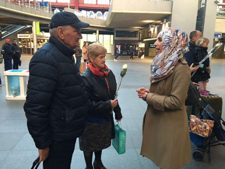 Leden van de Antwerpse moslimgemeenschap delen rozen uit op de Grote Markt in Antwerpen.