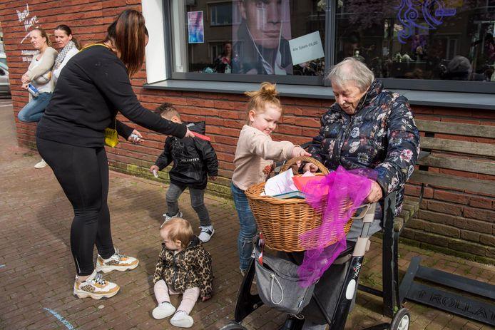 Kinderen uit de Tongelrese wijk Doornakkers in Eindhoven vullen de mand met kaarten die bewoonster Resie Somers van Berckelhof bij zich had.