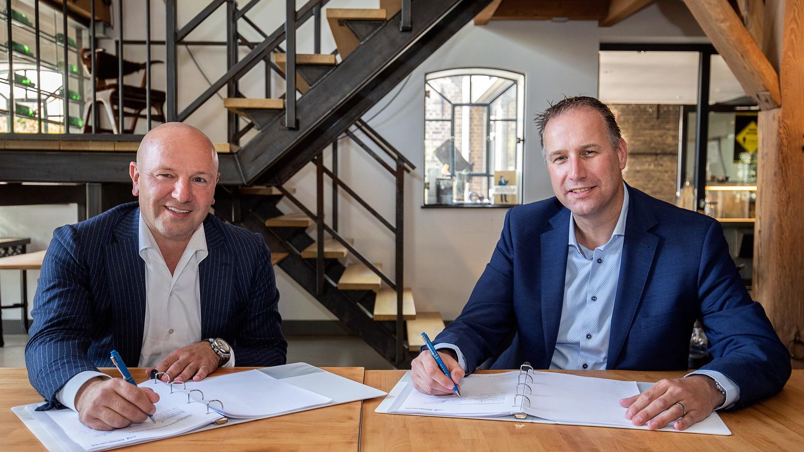 Edward Koornneef van Samen Ontwikkelen Westland (links) en Arie Houweling van Slavenburg Bouw zetten hun handtekening voor de realisatie van De Rentmeester in Naaldwijk.