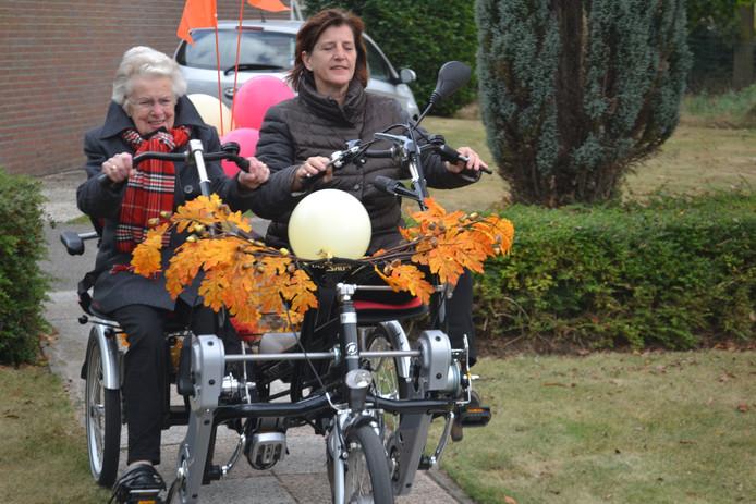 Mevrouw Thijssen en locatiemanager Janneke Pander maken het eerste ritje met de nieuwe duo-fiets.