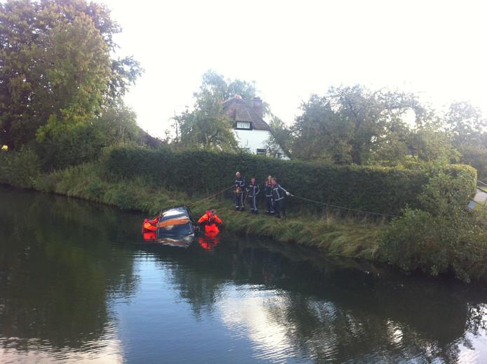 De auto wordt uit het water gehaald bij Terwolde. Het is onduidelijk hoe deze hier in het water is terecht gekomen.