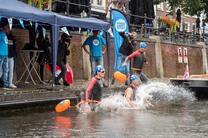 Breda - Pix4Profs/René Schotanus. Burgemeester Paul Depla (R), wethouder Daan Quaars (M) en oncoloog Hans Westgeest springen in het water voor Swim to Fight Cancer. Bij deze sprong raakt Paul Depla gewond aan zijn voet.