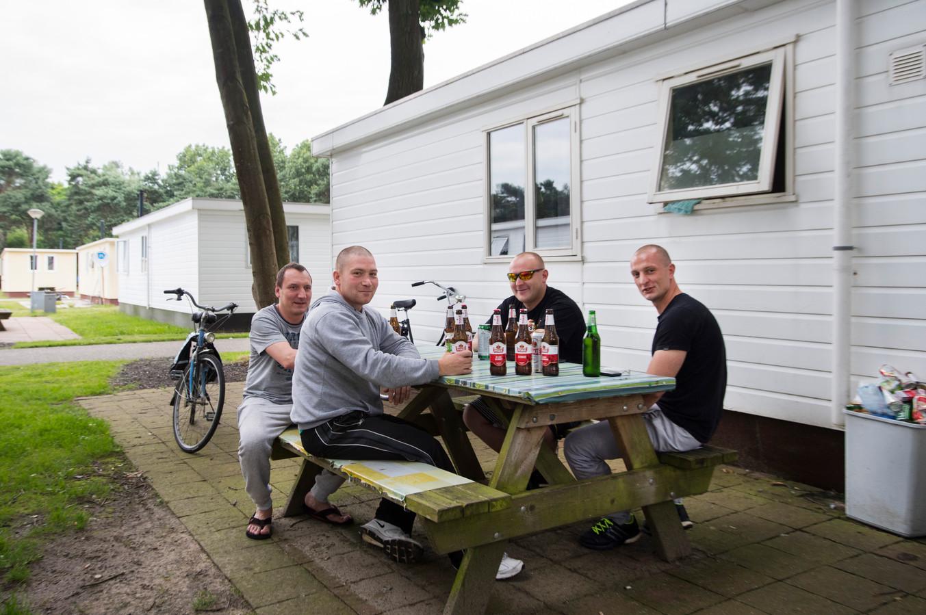 Poolse arbeidsmigranten bij hun woning op een recreatiepark in Oss, op een archiefbeeld uit 2006.