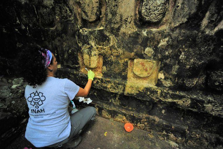 Een medewerkster van het Mexicaanse nationale instituut voor archeologie INAH is bezig met de restauratiewerkzaamheden.