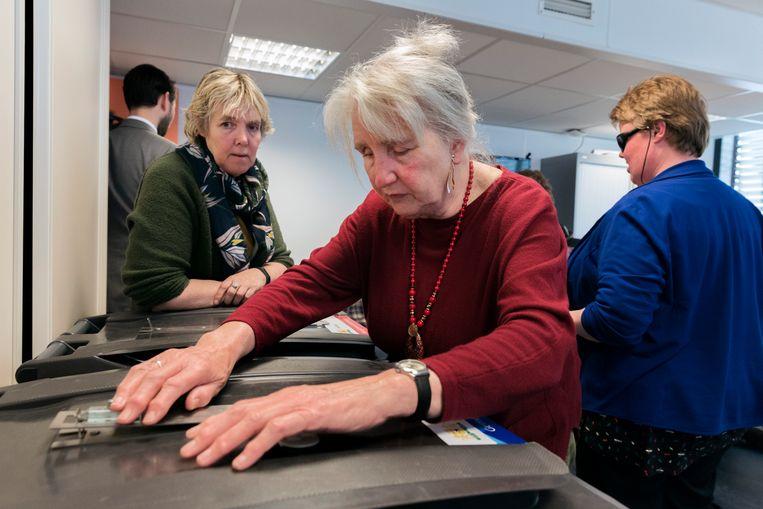 Bartiméus in Den Haag heeft een stembureau nagebouwd voor een cursus stemmen voor blinden en slechtzienden. Rechts staat Helma van der Boom.  Beeld Inge van Mill