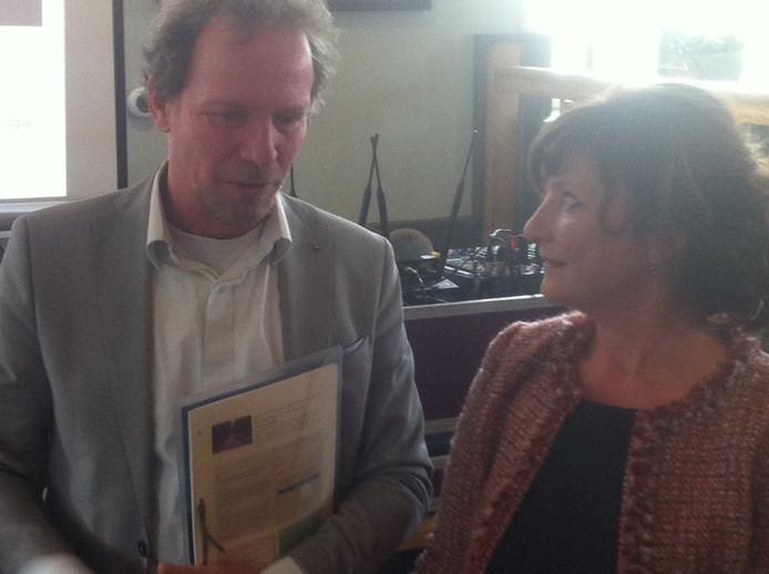 Gedeputeerde Johan van den Hout (links) met de petitie en Hannie Stappers van de actiegroep.