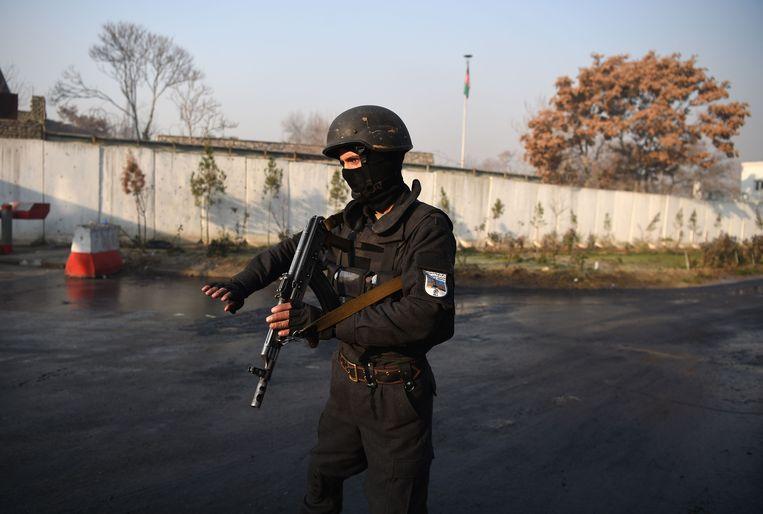 Een zwaargewapende Afghaanse beveiliger dinsdag bij het ministerie van Openbare Werken. Beeld AFP