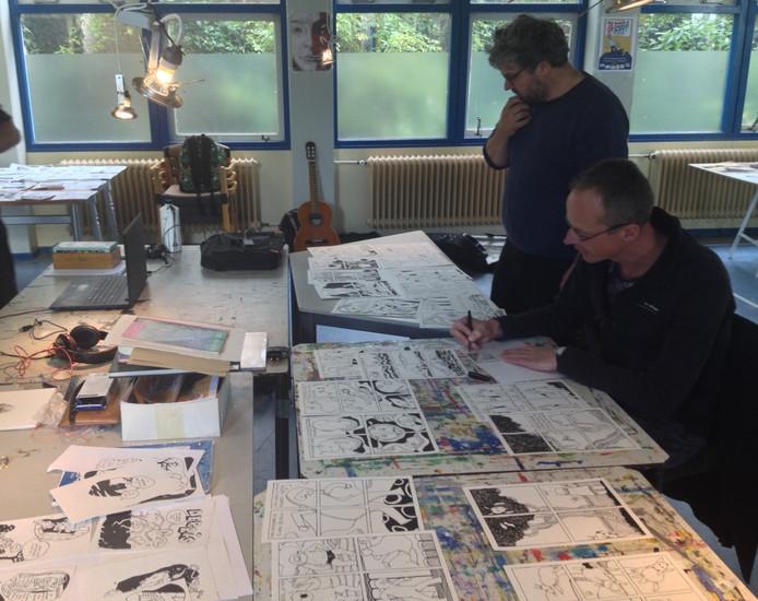 Jeroen Kersouw (zittend) en Ramon de Nennie tijdens de laatste uurtjes van de striptekenmarathon.