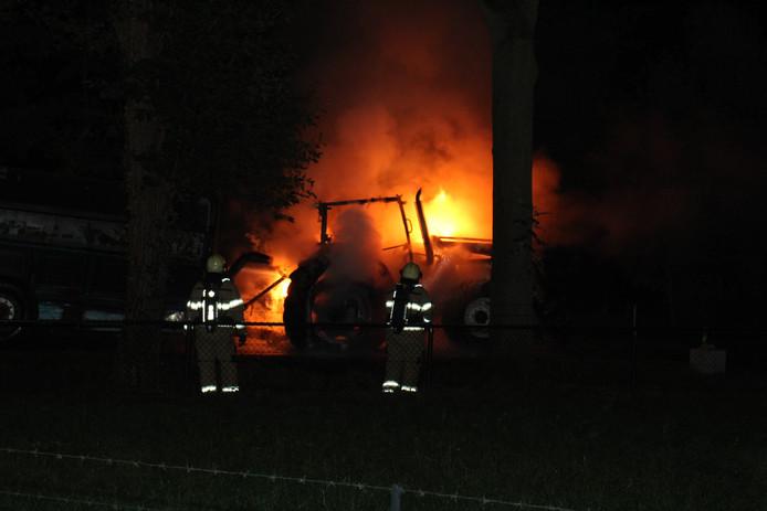 De brandweer bezig met het blussen van de brandende tractor.