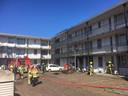 De brandweer onderzoekt of het vuur ook echt uit is in het appartement in de Waterstraat in Nijmegen.
