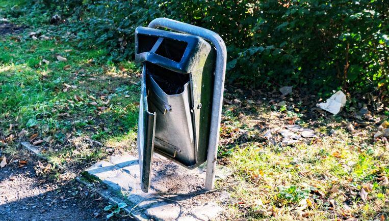 Een (door vandalen?) beschadigde vuilnisbak in het park.