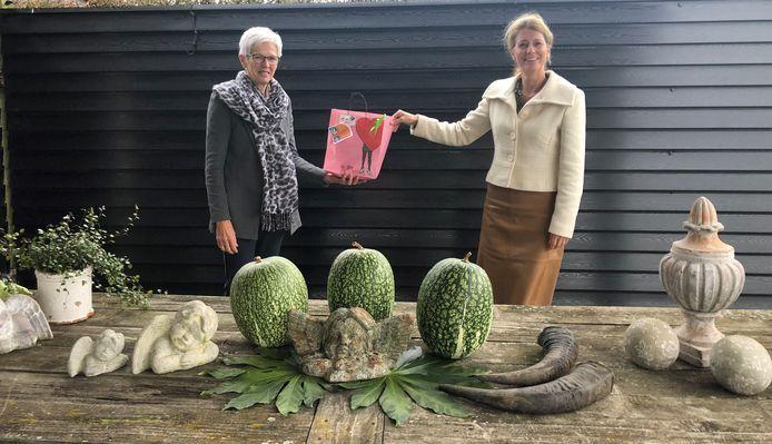 Wethouder Anita Sørensen van Maasdriel overhandigt een cadeautje aan mantelzorger Corry Prinsen.