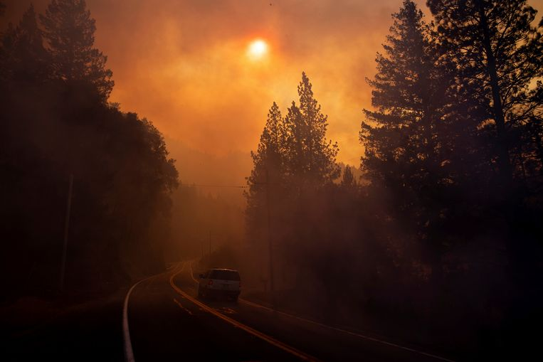 Een auto rijdt door de rook van de branden heen.