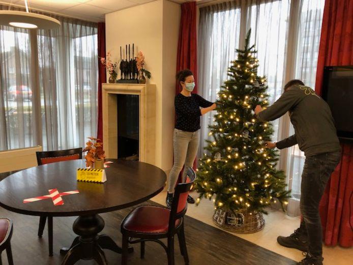 In een  hoek van de ontmoetingsruimte van De Watersteeg maken Bianca van der Stappen van BrabantZorg en een medewerker van Intratuin een kerstboom in orde.