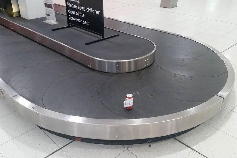 Het bierblikje op de transportband in de luchthaven van het Australische Perth.