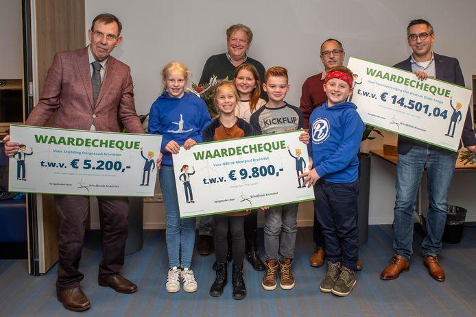 De voorzitters van de dorpsraad Bruinisse, de tennisvereniging uit Oude-Tonge en de directeur met leerlingen van De Meerpaal namen de symbolische cheques van het windfonds in ontvangst.