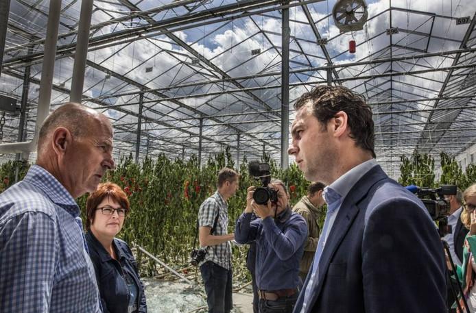 Staatssecretaris Martijn van Dam in gesprek met paprikateler Jo Joosten in zijn vernielde kas in Someren. Foto Ton van de Meulenhof