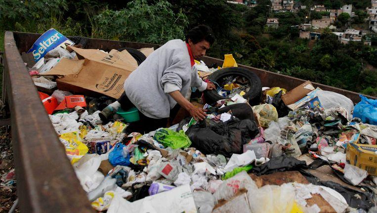 Een Hondurese man zoekt naar voedsel op een vuilnisbelt.