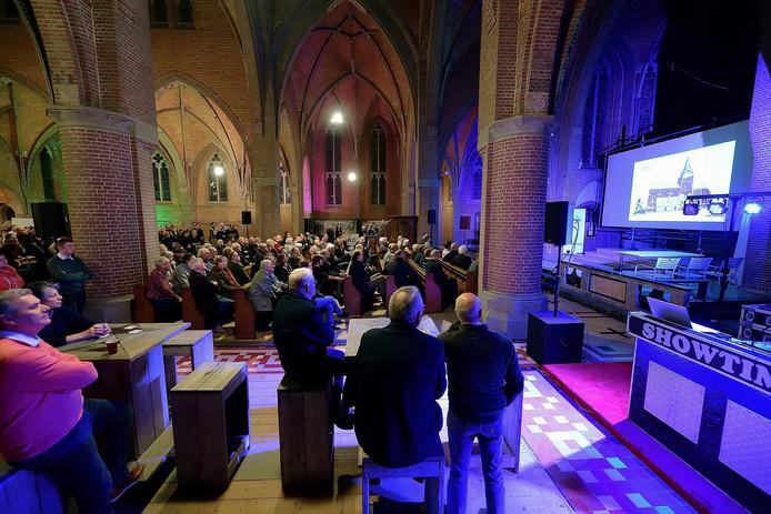 Een bomvolle kerk van Stampersgat kijkt mee als op het grote scherm de bouwplannen voor de kerk worden gepresenteerd.