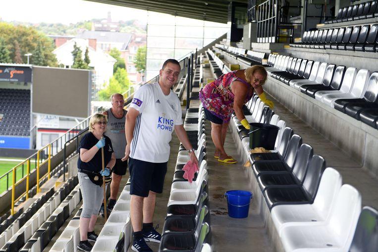 Supporters van OHL poetsen de tribunes van het stadion.