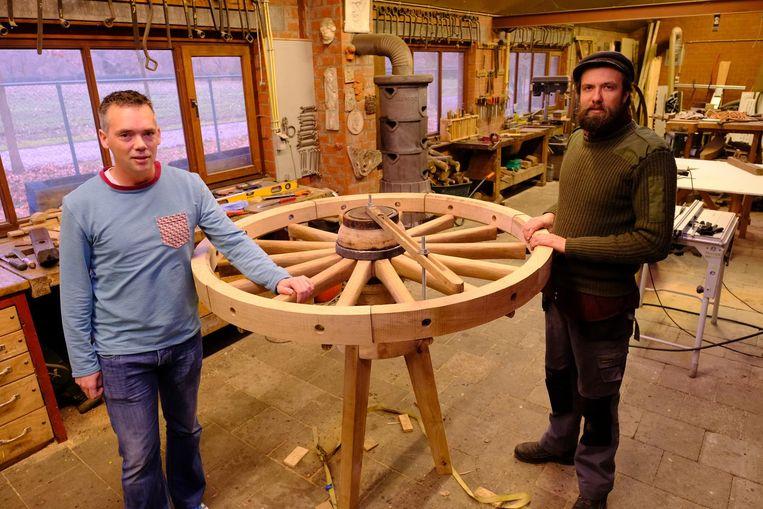 Afscheidnemend directeur Leo van den Berg en collectiebeheerder Dieter van Mol in het atelier van het museum bij een houten karrenwiel.