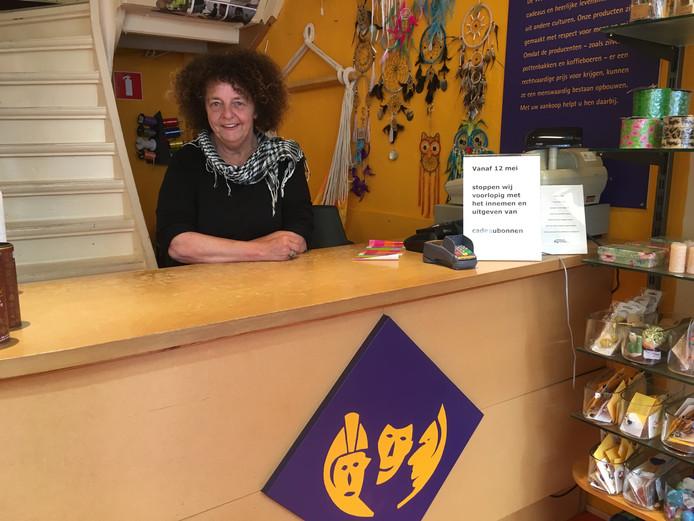 """Heleen Schreurs achter de toonbank van haar Wereldwinkel in Deventer. Een bordje maakt duidelijk dat cadeaubonnen er niet meer worden geaccepteerd. ,,Ze maken er een zootje van."""""""