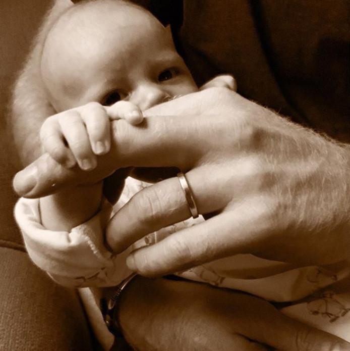 Archie in de armen van zijn vader.