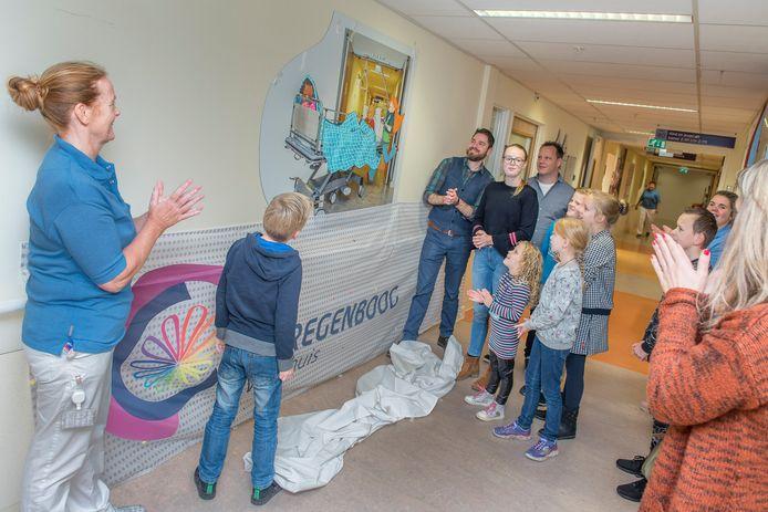 Kunstenaar Paul Oole (blauw giletje) verrichtte samen met leerlingen van De Regenboog de onthulling van de kunstmuur.