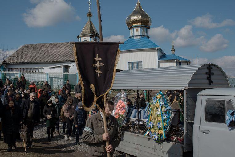 Inwoners van Bar sluiten zich aan bij de processie voor soldaat Roeslan Slisarenko. Zijn kist staat achter in de grijze wagen.   Beeld null