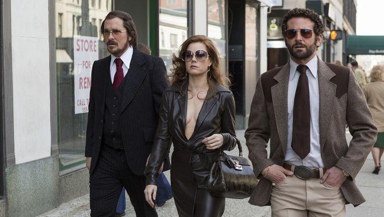 Christian Bale (l) als Irving Rosenfeld, Amy Adams als Sydney Prosser en Bradley Cooper als Richie Dimaso Beeld Still uit American Hustle