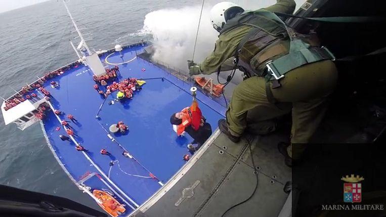Een vrouw wordt vanaf het dek van de Norman Atlantic in een helikopter getakeld. Beeld ap